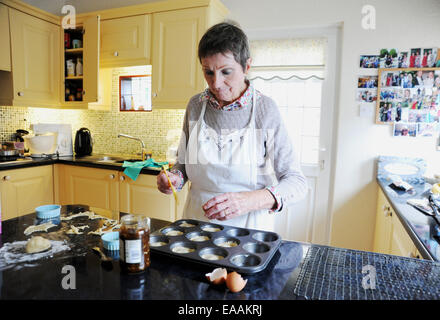 Elderly woman pensioner baking mince pies at home in her kitchen for Christmas - Stock Photo