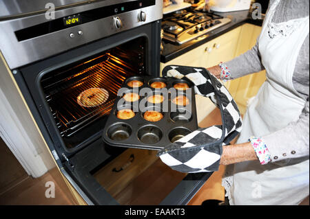 Elderly woman pensioner baking mince pies at home in her kitchen for Christmas . Taking the cooked pies out of the - Stock Photo