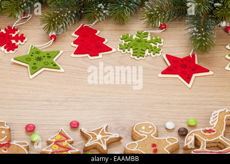 Christmas fir tree, cookies and decor on wooden board with copy space - Stock Photo
