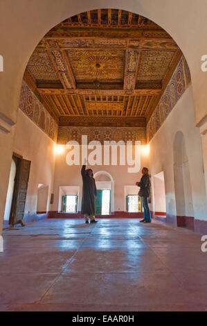 Vertical portrait of a tour guide and tourist inside the Kasbah Taourirt in Ouarzazate. - Stock Photo