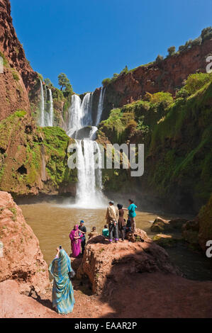 Vertical view of a traditional Moroccan family taking photos at Cascades d'Ouzoud on a sunny day. - Stock Photo