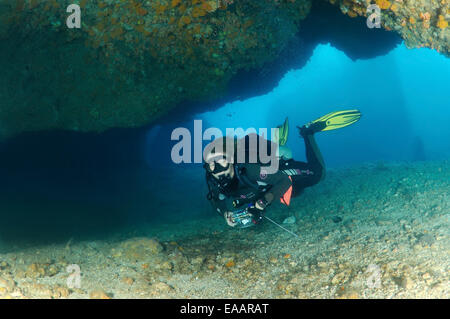 Diver looking into the cave. Bohol Sea, Cebu, Philippines, Southeast Asia - Stock Photo