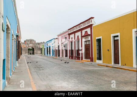 Restored colorful Spanish colonial houses and Land Gate (Puerta de Tierra) viewed from 59th Street, Campeche, Mexico. - Stock Photo