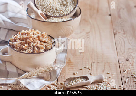 Ptititm or israeli couscous - kind of small pasta, traditional for israelian cuisine. Copy space background. - Stock Photo