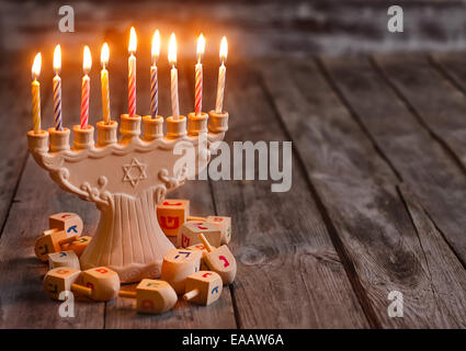 Jewish holiday hannukah symbols - menorah and wooden dreidels. Copy space background. - Stock Photo