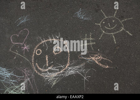 A face, a heart, a sun and a number sign. Child's drawings drawn by colour chalk on asphalt in Leipzig, Saxony, - Stock Photo