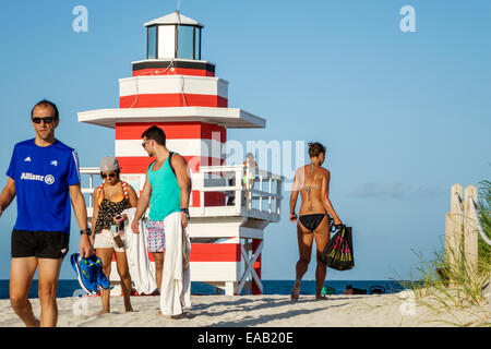 Miami Beach Florida sand lighthouse shaped lifeguard station Atlantic Ocean water sand man woman sunbathers - Stock Photo
