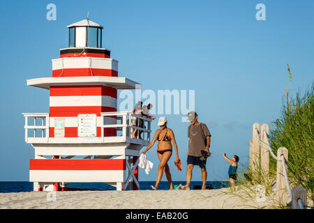 Miami Beach Florida sand lighthouse shaped lifeguard station Atlantic Ocean water sand man woman couple sunbathers - Stock Photo