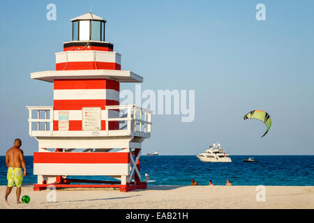Miami Beach Florida sand lighthouse shaped lifeguard station Atlantic Ocean water sand man boat yacht - Stock Photo