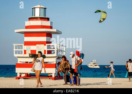 Miami Beach Florida sand lighthouse shaped lifeguard station Atlantic Ocean water sand woman man sunbathers boat - Stock Photo