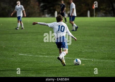 Youth soccer player takes a free kick during a match game. - Stock Photo