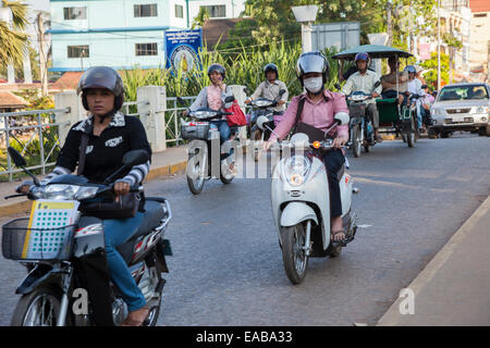 Cambodia, Siem Reap.  Street Traffic.  Woman Using Cell Phone, another with Breathing Mask. - Stock Photo