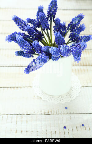 Hyacinth in a white vase on wooden boards, flowers - Stock Photo