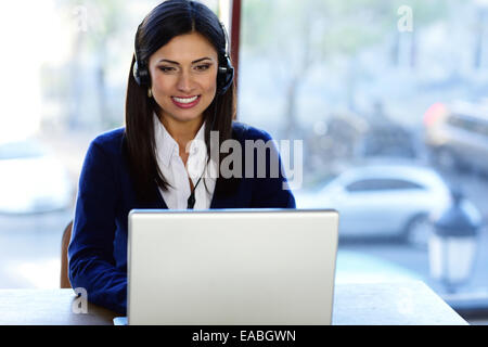 Cheerful beautiful call-center assistant at the desk - Stock Photo