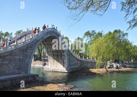Tourists pass by XIUYI arch bridge in Summer Palace - Stock Photo