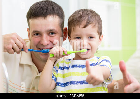 dad and child son brushing teeth in bathroom - Stock Photo