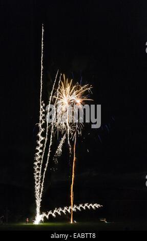 Man launching fireworks at a village firework display, UK - Stock Photo