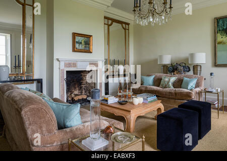 Large antique mirrors in airy sitting room with fireplace and pair of Kingscome sofas upholstered in taupe linen - Stock Photo