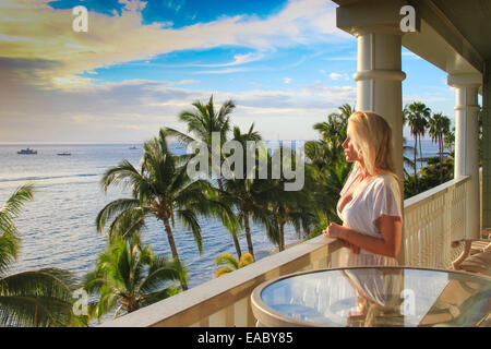 Attractive blonde lady in a tropical setting overlooking the beautiful sea from a balcony - Stock Photo
