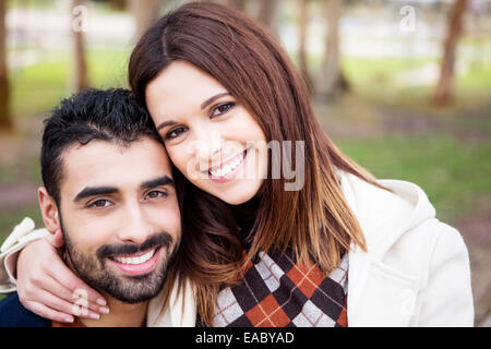 Young romantic couple on a bench in park - Stock Photo