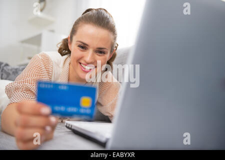 Happy young woman making online shopping - Stock Photo