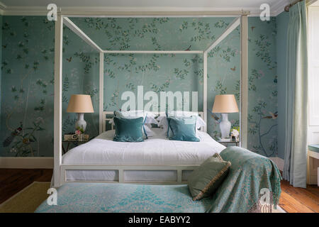 de Gournay Chinoiserie silk wallpaper in elegant bedroom with four poster bed from Ochre and sisal rug - Stock Photo