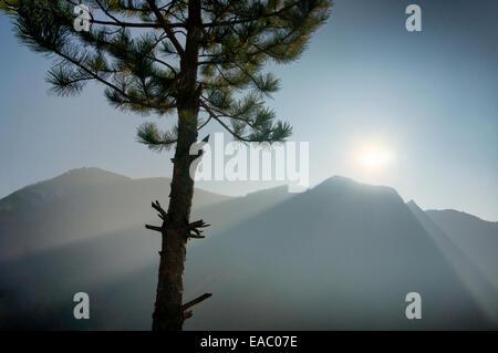 The light of the sun shinning over the mountain ridge creating heavenly rays. - Stock Photo