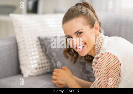 Portrait of happy young woman laying on sofa - Stock Photo