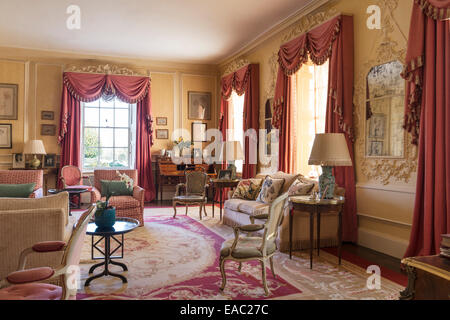 Dusty pink coloured curtains with swags and tails in elegant drawing room with Louis XVI style armchairs and large - Stock Photo