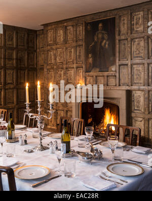 Original Jacobean wall panels in dining room with open fireplace - Stock Photo