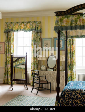 Antique wooden four poster bed with floral patterned fabrics - Stock Photo