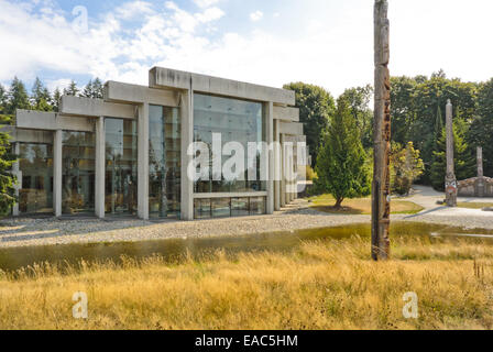 View of Museum of Anthropology grounds with totem poles and First Nations' house in background - Stock Photo
