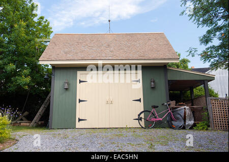 Pink bicycle propped up against a green and yellow wooden garage. - Stock Photo
