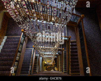 A huge chandelier in a hotel made up of crystals and beads descends many stories to ground level. - Stock Photo