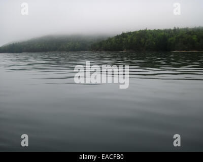 Fog rolls in on a spring morning over Lake Jocassee - Stock Photo