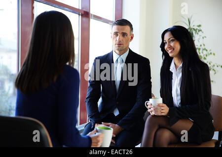 Happy businesspeople having coffee break in office - Stock Photo