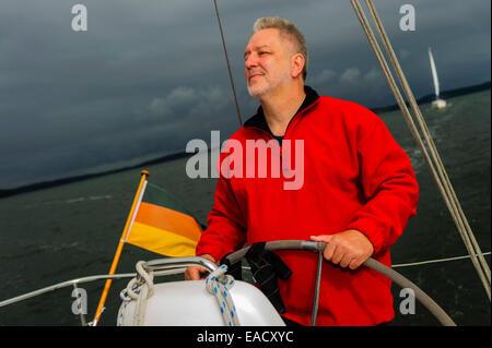 Skipper standing at the helm of his yacht, Strelasund, Stralsund, Mecklenburg-Western Pomerania, Germany - Stock Photo