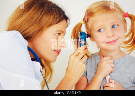 Pediatrician doctor examining little girl`s ears. - Stock Photo