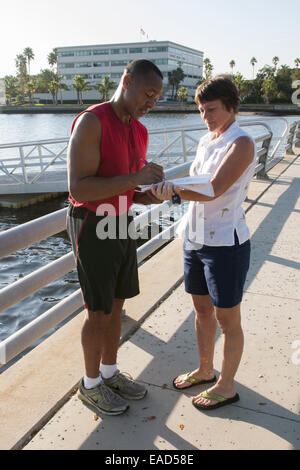 African American man signing a paper on the riverwalk at Rossi Park in Bradenton, Florida, USA - Stock Photo