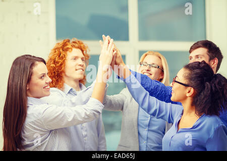 creative team doing high five gesture in office - Stock Photo