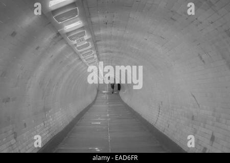Man walking through Greenwich foot tunnel that runs under the River Thames between Greenwich and Isle of Dogs London - Stock Photo