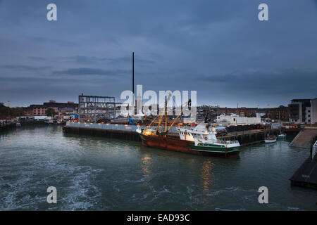 Trawler moored in Portsmouth Harbour with working lights in the pre dawn - Stock Photo