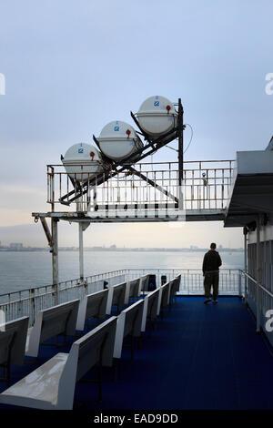Man on car ferry deck under Zodiac Liferaft deployment slide - Stock Photo