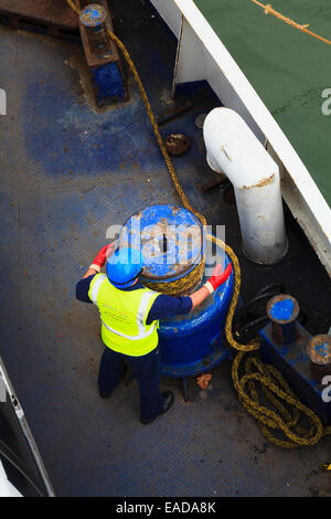 Looking down on crew member using mooring rope winding winch - Stock Photo
