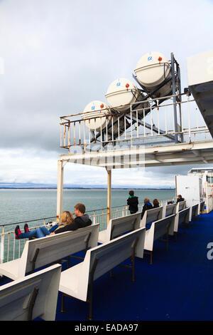 Passengers sitting on seats on a deck of a ferry under a Zodiac Liferaft deployment slide - Stock Photo