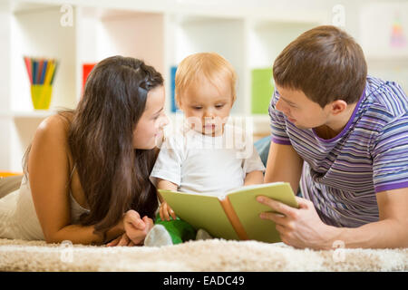Young parents mom and dad reading children book to baby boy - Stock Photo