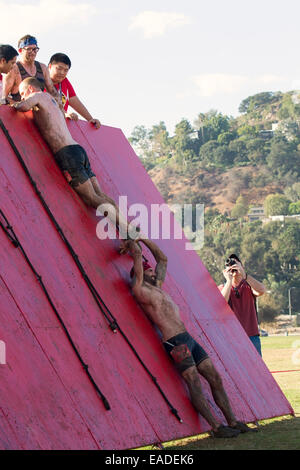 Participants scale the 'Wall of shame' in the Spartan 'Gladiator Rock'n Run'  5k obstacle course Pasadena, California - Stock Photo