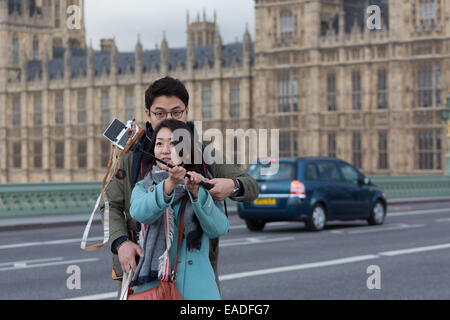 Asian couple take a selfie using a 'selfie stick' with the Palace of Westminster in the background - Stock Photo