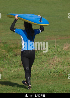 Young woman carrying a surfboard on her head, Bude, Cornwall, UK - Stock Photo
