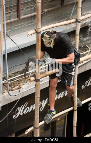 Man building scaffolding by tying lengths of bamboo together, Hong Kong. - Stock Photo